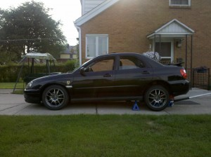 car jacked up under the rear differential and jack stands underneath in front of rear wheels on WRX