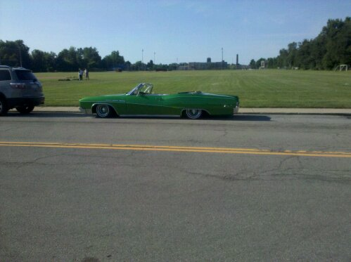 green convertible lowrider on the ground with air suspension and cool wheels