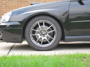 RCE Yellow springs front wheel side view, D-Spec struts, cut bump stops, 2004 Subaru WRX Sedan