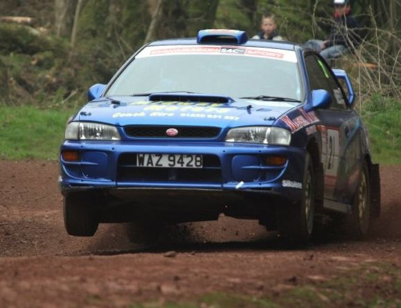 blue Subaru Impreza GC WRX STI rally car doing wheelie